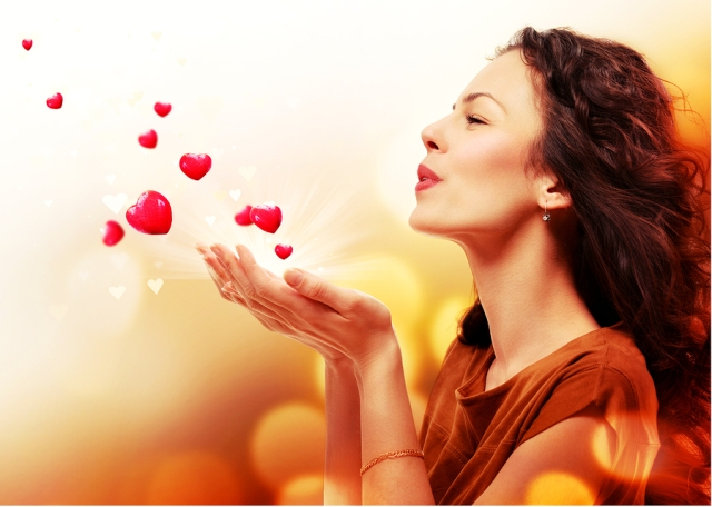 Beauty Young Woman Blowing Hearts from her Hands. St. Valentines Day Concept. Beautiful Girl in Love